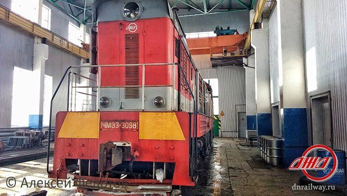 Тепловоз стоит в депо Донецкая Железная дорога красно серый поезд сине серые стены депо